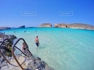 水の体の横に立っている人の写真・画像素材[1388208]