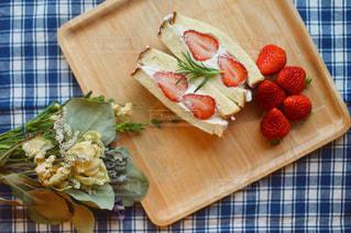 木製のまな板の上にフルーツとケーキの写真・画像素材[2140813]
