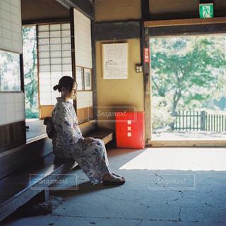 窓の前でベンチに座っている人の写真・画像素材[1452621]