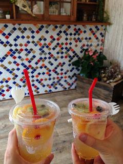 コーヒー カップの横にあるオレンジ ジュースのガラスの写真・画像素材[713706]