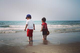 海の横にあるビーチの上を歩く男の写真・画像素材[717015]