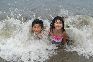 海でサーフボードで波に乗って若い女の子の写真・画像素材[1352926]