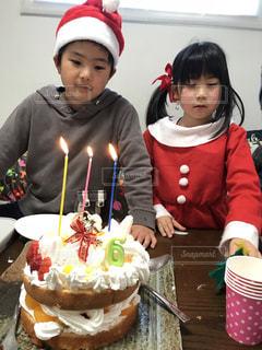 誕生日ケーキの前に立っている人の写真・画像素材[1668525]