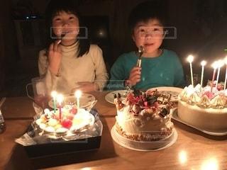 キャンドルとバースデー ケーキでテーブルに座っている人の写真・画像素材[1689136]