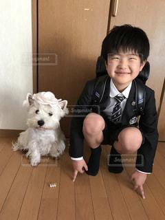 犬の横に立っている小さな男の子の写真・画像素材[2078705]