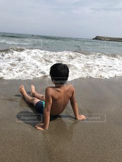 浜辺に座っている若い男の写真・画像素材[2356449]