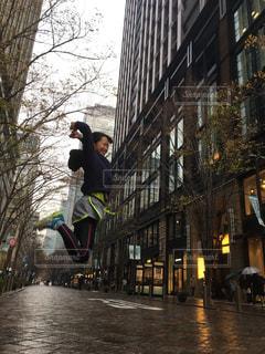 通りの真ん中でジャンプする女性の写真・画像素材[1717796]