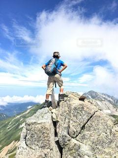 岩が多い丘の上に立っている人の写真・画像素材[770894]