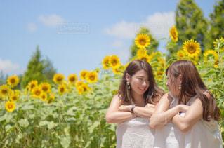 花の前に立っている女性の写真・画像素材[720849]