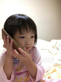 電話で話してベッドに座っている少女の写真・画像素材[740085]
