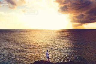 水の体の横に立っている人の写真・画像素材[934011]