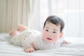 ベッドでうつ伏せになっている赤ちゃんの写真・画像素材[3362442]