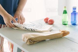 テーブルでエコバッグをたたむ男性の写真・画像素材[4408848]