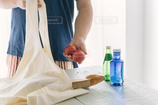 テーブルでエコバッグを持つ男性の写真・画像素材[4408847]