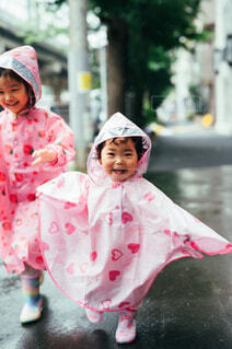 レインコートを着て走る姉妹の写真・画像素材[4576903]