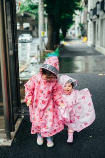 レインコートを着て歩く姉妹の写真・画像素材[4576926]