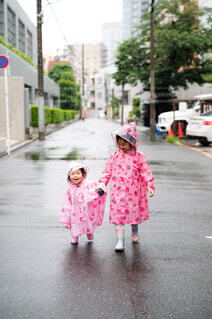 レインコートを着て歩く姉妹の写真・画像素材[4576935]