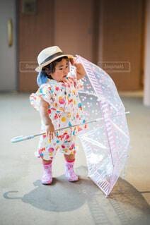 玄関前で雨傘を持つ子供の写真・画像素材[4610309]