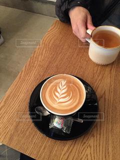 木製のテーブルの上に座っているコーヒー1杯の写真・画像素材[2278768]