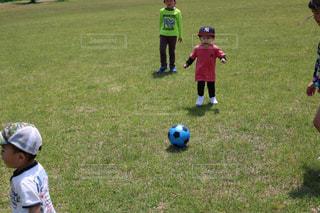 フィールド上にサッカー ボールを抱いて少年の写真・画像素材[1177005]