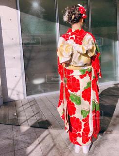 花瓶の横に立っている赤と白のドレスの写真・画像素材[1724594]