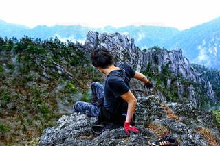 岩が多い丘の上に立っている人の写真・画像素材[770412]