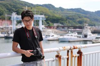 フェンスの横に立っている少年の写真・画像素材[894599]