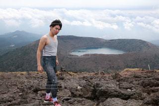 岩が多い丘の上に立っている人の写真・画像素材[894616]