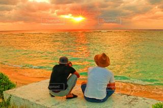水の体の近くのビーチに座っている男の写真・画像素材[915820]
