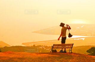 バック グラウンドで夕日を持つ男の写真・画像素材[956294]