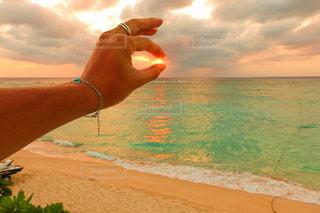 水の体の近くのビーチに立っている人の写真・画像素材[956302]