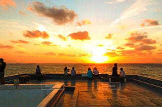 ビーチでの背景の夕日に人々 のグループの写真・画像素材[956305]