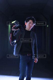暗闇の中に立っている男の人の写真・画像素材[1016047]