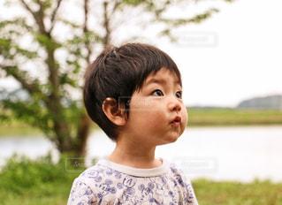 草の中に立っている小さな男の子の写真・画像素材[1016055]