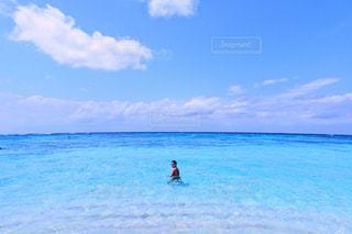 海の横にある水の体の横に立っている人の写真・画像素材[1101112]