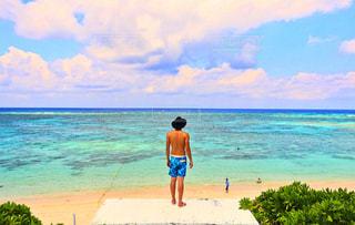 水の体の近くのビーチに立っている人 - No.1101114