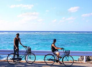 水の体の近くのビーチで自転車に乗る人の写真・画像素材[1101115]