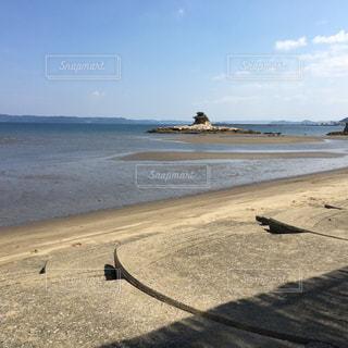 水の体の横にある砂浜のビーチの上に横たわる - No.729197
