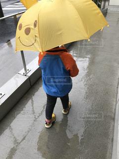 傘を持って雨の中で立っている少年の写真・画像素材[814984]