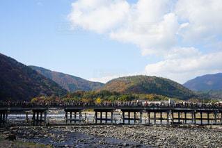 背景の山が付いている水の体の上の橋の写真・画像素材[909536]