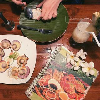 食品のプレートをテーブルに座っている女性 - No.920092