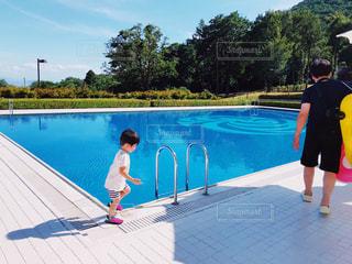 水のプールの横に立っている人の写真・画像素材[1468098]