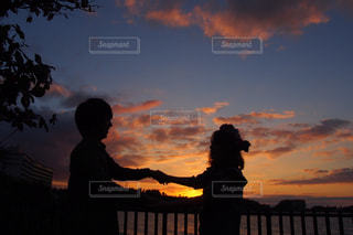 日没の前に立っている人々 のグループの写真・画像素材[747639]