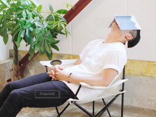 椅子に座って読書中に寝ている男性の写真・画像素材[2571035]