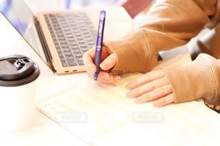女性,コーヒー,屋内,室内,手,ペン,机,パソコン,人,ノート,勉強,PC,ビジネス,手書き,電化製品,コンピューター,モノ,リモートワーク,ビジネスシーン