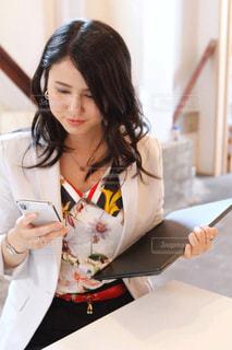 綺麗な女性がPCと携帯を持って屋内でお仕事中の写真・画像素材[2588705]