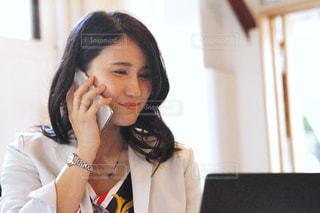 携帯で話す仕事中の笑顔の女性の写真・画像素材[2603824]