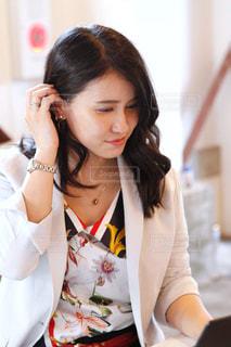髪をかきあげて微笑む仕事中の女性の写真・画像素材[2603889]