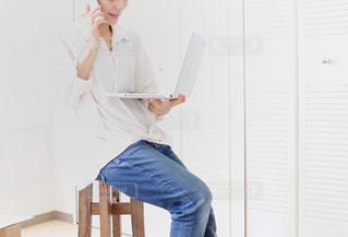 携帯とPCで仕事をする女性の写真・画像素材[2650759]