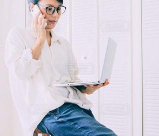 リモートワーク 部屋でPCを持って携帯で話す女性の写真・画像素材[2651628]